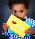 African schoolboy portrait cute little child with holding book with text i love school on blackboard background for the first time Stock Photos