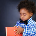 African schoolboy portrait of serious adorable opening book over dark background copy space back to school Stock Images