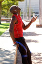 African sportsman at the park laughing with mobile phone Royalty Free Stock Photo