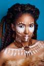 African style . Attractive young woman in ethnic jewelry . close up portrait of a woman with a painted face. Creative make up