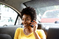 African woman in a car talking on mobile phone close up portrait of smiling young sitting back seat of Royalty Free Stock Images