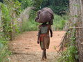 African woman carrying a bag of goods on her head Stock Photo