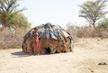 African woman of the dasanech or galeb ethnic group is standing outside the hut in the village along the road to turkana lake Royalty Free Stock Photo