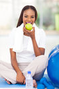 African woman eating apple young american after exercise Stock Images