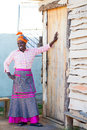African woman shows her home proud leaning against homes door smiling brightly Stock Image