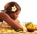 African woman at spa photo of lovely with closed eyes and white franjipani flower in head relaxed on massage table in luxury salon Stock Images
