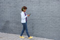 African woman walking and listening to music on mobile phone Royalty Free Stock Photo