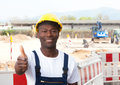 African worker at construction zone showing thumb up friendly laughing with excavator in the background Stock Photos
