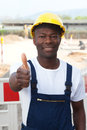 African worker at construction zone showing thumb up friendly laughing with excavator in the background Royalty Free Stock Photos