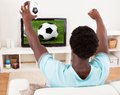 African young man watching television holding football happy match in at home Royalty Free Stock Photos