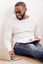 Afro american man at home handsome in glasses is making notes using a laptop and smiling while sitting on the floor Royalty Free Stock Images