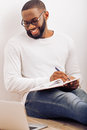 Afro american man at home handsome in glasses is making notes using a laptop and smiling while sitting on the floor Stock Image