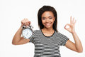 Afro american woman holding alarm clock and showing ok gesture Royalty Free Stock Photo