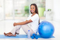 Afro american woman working out healthy sitting on mat after Stock Photos