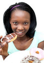 Afro-American young woman eating a chocolate donut Royalty Free Stock Image