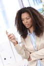 Afro businesswoman texting young on mobile phone in office Stock Images