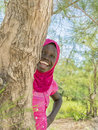 Afro girl playing hide and seek behind a filao tree ten years old Royalty Free Stock Photography