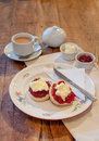 Afternoon tea with scones jam and clotted cream portrait format picture of on floral plate oak table Royalty Free Stock Photo