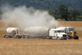 Ag lime large semi truck loads up a big tire agricultural spreader with Stock Photos