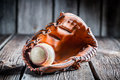 Age baseball glove and ball on old wooden table Stock Photos