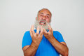 Aged bearded man grimacing at the camera expressing extreme nervousness Royalty Free Stock Photo
