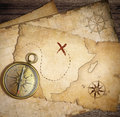 Aged brass nautical compass on table with old maps treasure Stock Photo