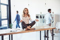 Aged businesswoman sitting on table and meditating in lotus position while colleagues working behind Royalty Free Stock Photo