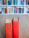 Aged copies of sherlock holmes stories long and short standing on a wooden table with a book shelf full books in soft focus Royalty Free Stock Photo