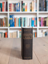 Aged copy of the complete works of shakespeare standing upright on a wooden table with a bookshelf full books in soft focus Royalty Free Stock Images