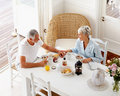 An aged couple enjoying their breakfast at home Stock Photos