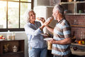 Aged couple having fun in the kitchen at breakfast time Royalty Free Stock Photo