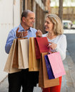 Aged couple with purchases smiling senior mature staying at street in hands Stock Photo