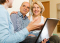 Aged couple talking with employee with laptop at home Stock Photography