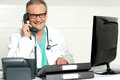Aged doctor attending call in front of lcd screen Royalty Free Stock Photo