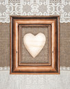 Aged frame with wooden heart on the burlap Royalty Free Stock Photo