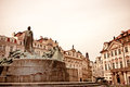 Aged image of central prague with a low angle view a figural fountain surrounded by historical buildings and architecture with Stock Photos