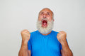 Aged man screaming in fury with clenched fists against white bac beard is mouth widely opened and isolated background Royalty Free Stock Images