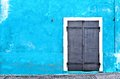 Aged metal door on blue wall - Warehouse Royalty Free Stock Photo