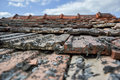 Aged roofing tiles on old house in village on blue cloudy sky Royalty Free Stock Photo
