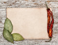 Aged sheet of paper with dry bay leaves and pepper on the old wooden background Royalty Free Stock Photo