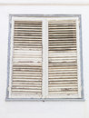 Aged white closed window shutters with peeling paint Royalty Free Stock Photo