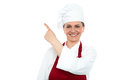 Aged woman chef pointing at copy space area Royalty Free Stock Photos
