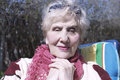 Aged woman smile nice portrait of sitting in a chair in her garden day light shot Stock Photos