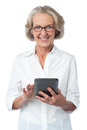 Aged woman using touch pad device senior citizen posing with tablet pc over white Stock Photography