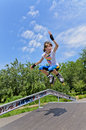 Agile young girl roller skating teenage jumping midair with her legs bent off a steep cement ramp at a skate park with a backdrop Royalty Free Stock Photos