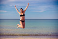 Agile young woman in a bikini leaping for joy attractive on beautiful tranquil tropical beach the summer sunshine as she Royalty Free Stock Image
