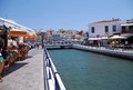 Agios nikolaos crete greece july cityview with outdoor greek taverns and bridge at july in small lagoon lake voulismeni of Stock Photography