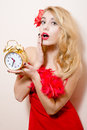 Agitated beautiful funny young blond pinup pretty woman with alarm-clock in red dress wonderingly looking at camera Royalty Free Stock Photo