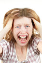 Agony young woman screaming in with mouth wide open holding head Stock Images
