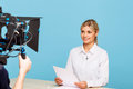 Agreeable tv announcer being involved in work live broadcasting pleasant professional attractive sitting at the table and holding Royalty Free Stock Photography